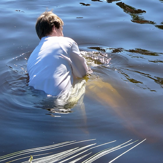 a pastor baptizing a believer in a lake, by immersion